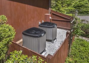 Backyard HVAC Units on Pebbles With Wooden Fence