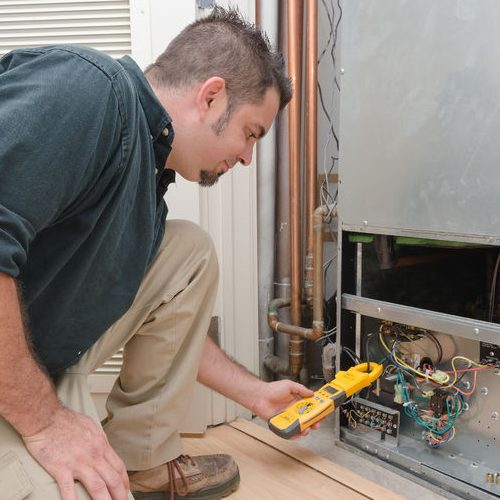 A Picture of an HVAC Technician Checking Heat Pump Amperage.