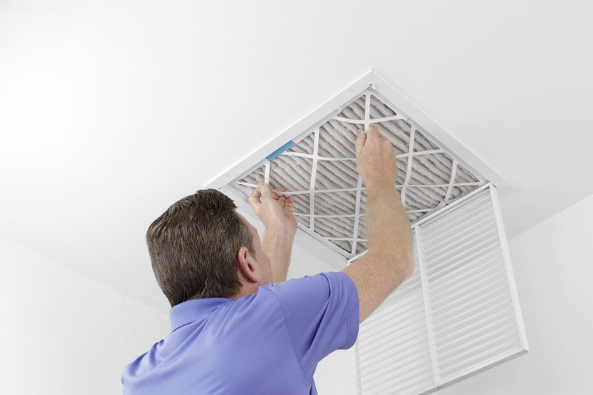 A Picture of a Man Removing a Dirty Air Filter.